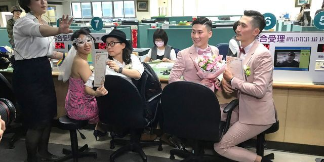 Two same-sex couples show their legal marriage certificates at the registration office in Xingyi District in Taipei, Taiwan, Friday, May 24, 2019. Hundreds of same-sex couples in Taiwan are rushing to the household registration office on the first day that a landmark decision to legalize same-sex marriage has taken effect.