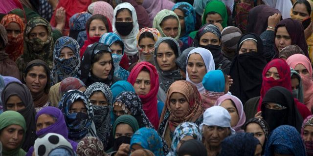 Kashmiri villagers watch the funeral procession of Zakir Musa, a top militant commander linked to al-Qaida, as it rains in Tral, south of Srinagar, Indian controlled Kashmir, Friday, May 24, 2019. (AP Photo/Dar Yasin)