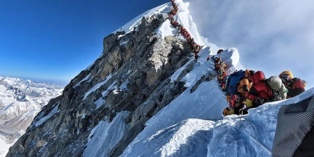 A line of climbers attempt to stand at the summit of Mount Everest. A British climber, Robin Haynes died on the mountain on Saturday.