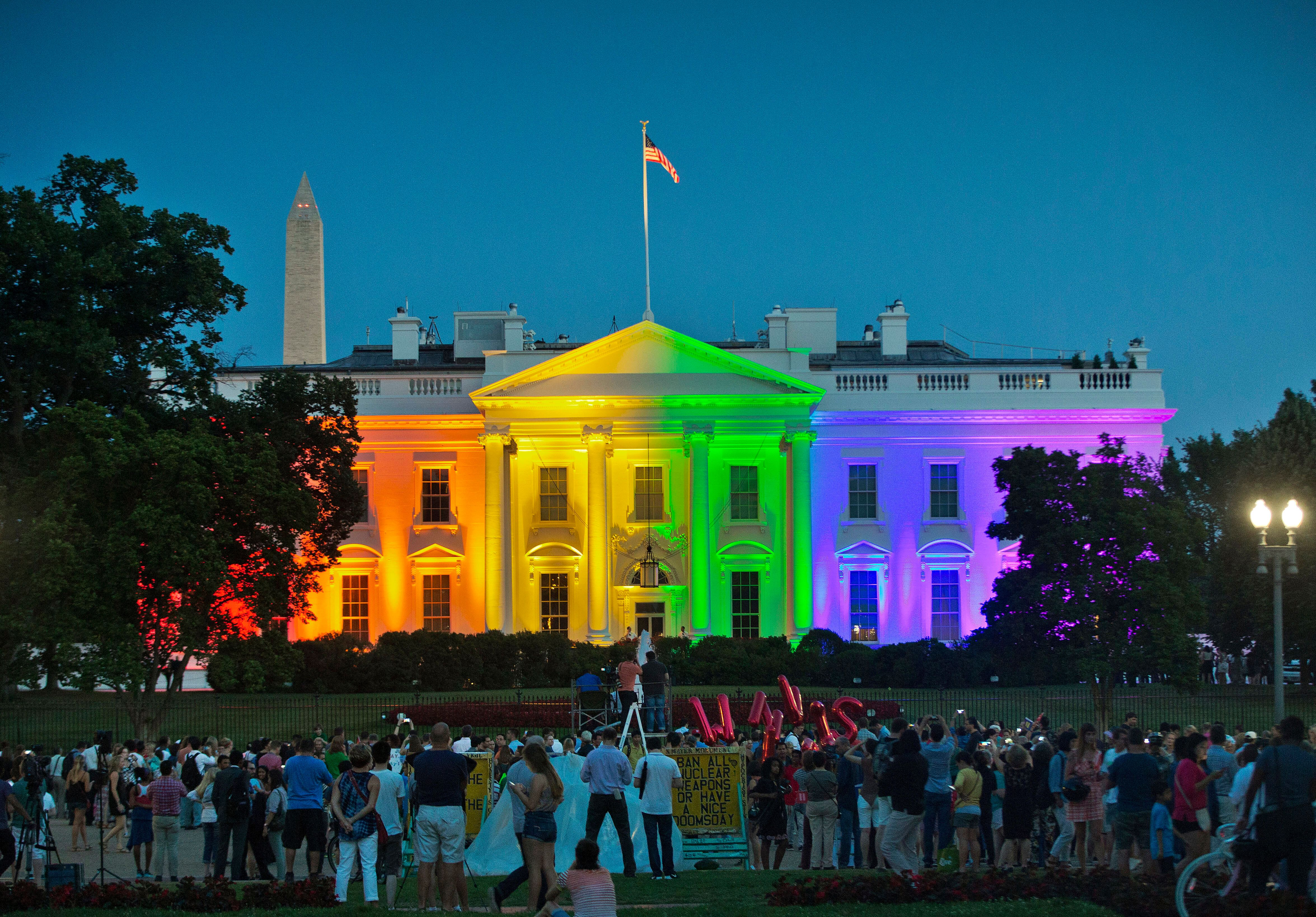 In this June 26, 2015, file photo, people gather in Lafayette Park to see the White House illuminated with rainbow colors in