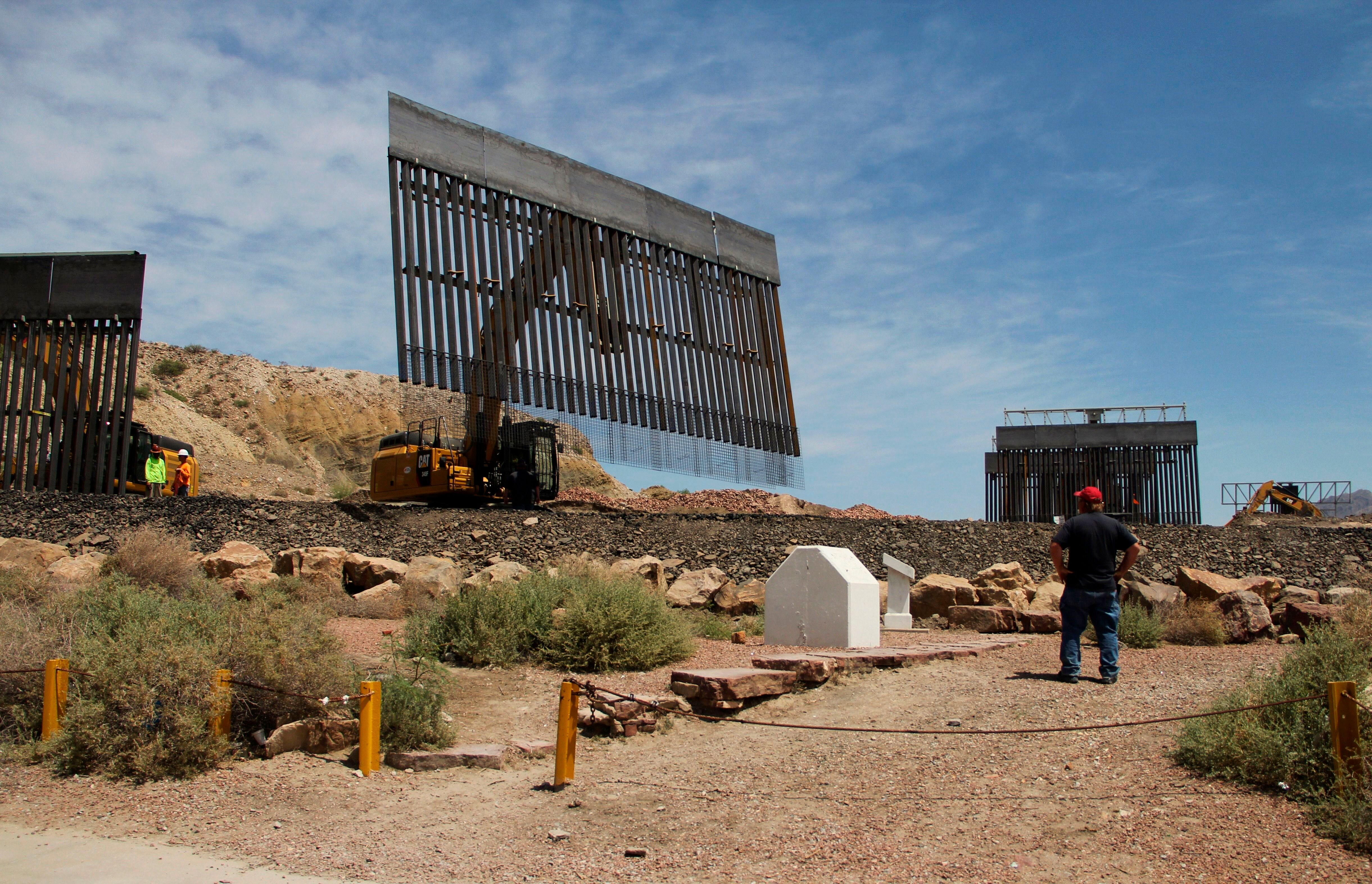 Workers build a border fence on private property located in the limits of Texas and New Mexico on Sunday.