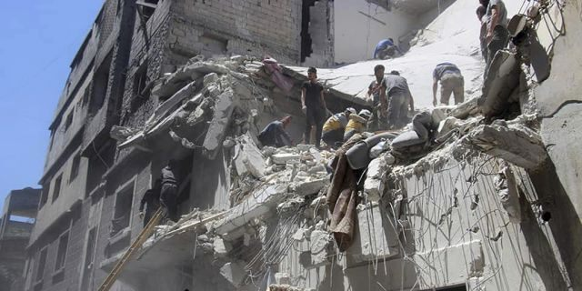 This photo provided by the Syrian Civil Defense White Helmets, which has been authenticated based on its contents and other AP reporting, shows Civil Defense workers inspecting a damaged building after an airstrike by Syrian government forces, in the town of Ariha, in the northwestern province of Idlib, Syria, Monday, May 27, 2019.