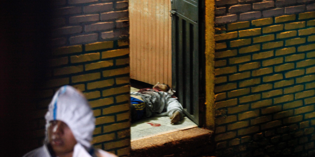 A body is stretched out at the door of a bar in the community of Comayaguela, Honduras, Friday, Oct. 19, 2018. At least eight people were killed and two other wounded at the bar Friday, according to the police. (AP Photo/Fernando Antonio)