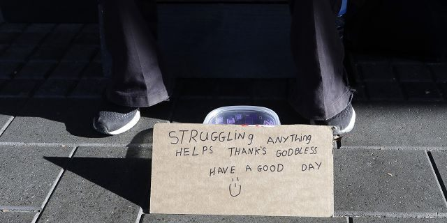 A man sits with a bowl asking for money in the central business district of Christchurch, New Zealand, Thursday, May 30, 2019.