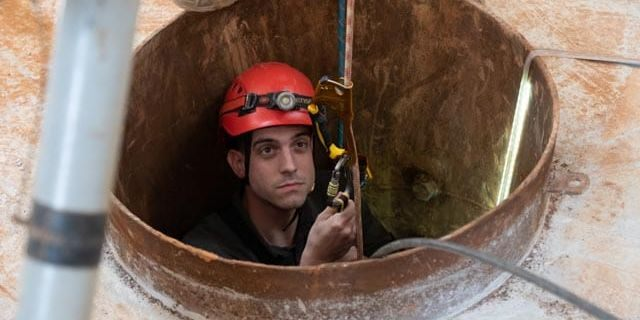 Trey Yingst being lowered into a Hezbollah tunnel using repurposed climbing equipment.