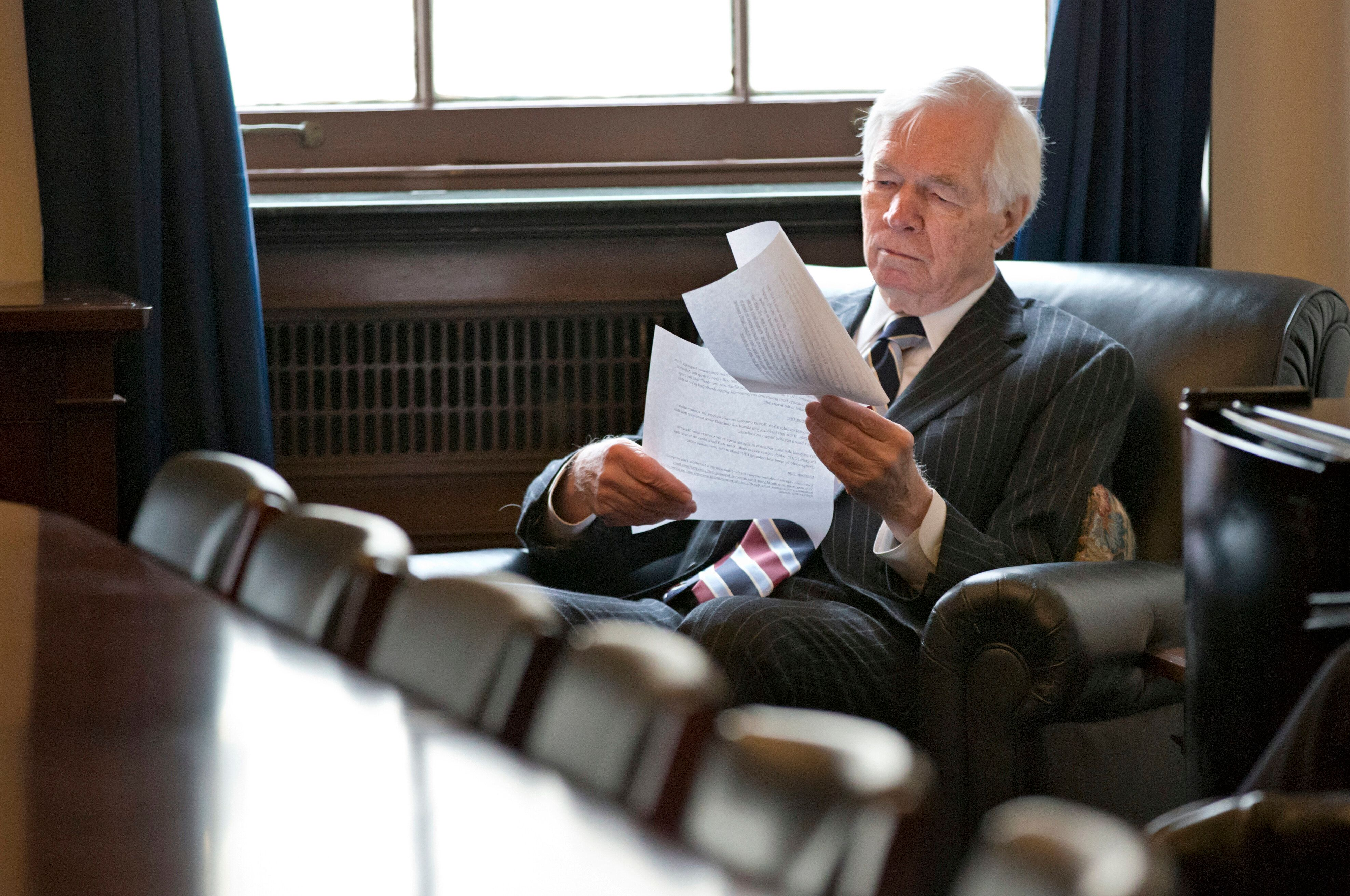 In this Dec. 4, 2013, file photo, Sen. Thad Cochran looks over documents before a closed-door meeting with other farm bill ne