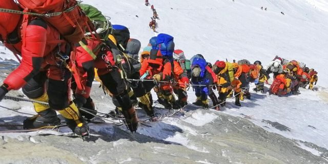 In this May 22, 2019 photo, a long queue of mountain climbers line a path on Mount Everest just below camp four, in Nepal.