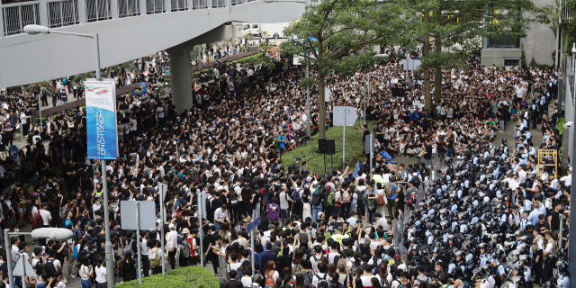 Protesters gather in front of policemen in anti-riot gear outside the Legislative Council in Hong Kong, Wednesday, June 12, 2019. Government officials in Hong Kong are bracing for a showdown as protesters and police continue to face off into the early morning hours outside the semiautonomous Chinese territory's legislature ahead of Wednesday's debate over changes allowing extradition to the Chinese mainland. (AP Photo/Vincent Yu)