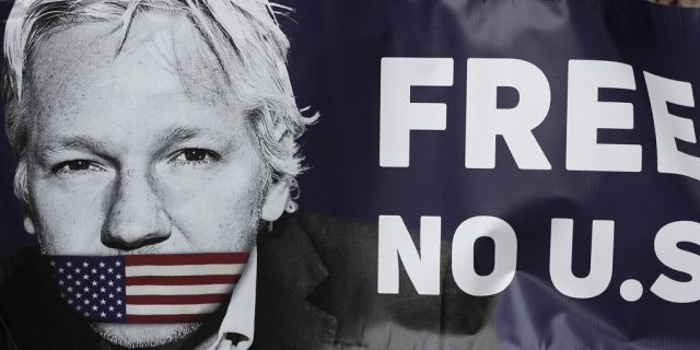 Assange supporters hold a banner to protest outside Westminster Magistrates Court in London, Friday, June 14, 2019.