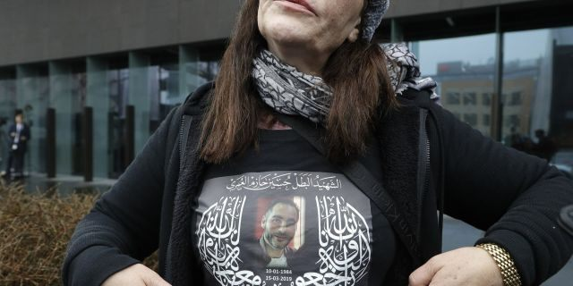 Janna Ezat, mother of Al Noor mosque shooting victim, Hussein Al-Umari shows a shirt bearing his photo outside the Christchurch District Court in Christchurch, New Zealand, Friday, June 14, 2019. Brenton Tarrant, the man accused of killing 51 people at two Christchurch mosques on March 15, 2019, pleaded not guilty to all the charges filed against him Friday June 14.