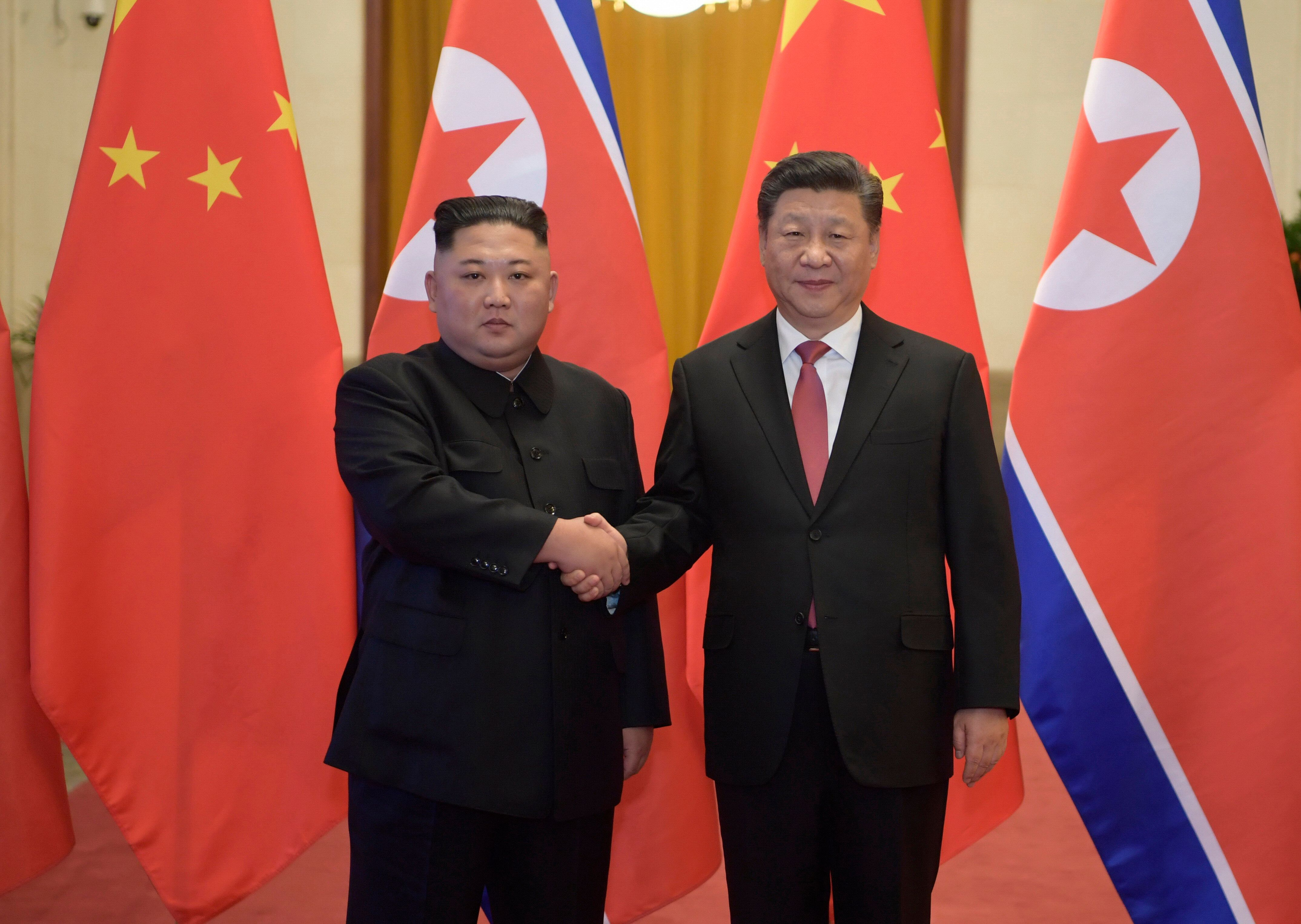 North Korean leader Kim Jong Un, left, and Chinese President Xi Jinping shake hands as they pose for a photo before talks at