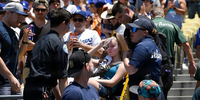 The fan was alert and answering questions after being struck by Bellinger's foul ball. (AP Photo/Mark J. Terrill)