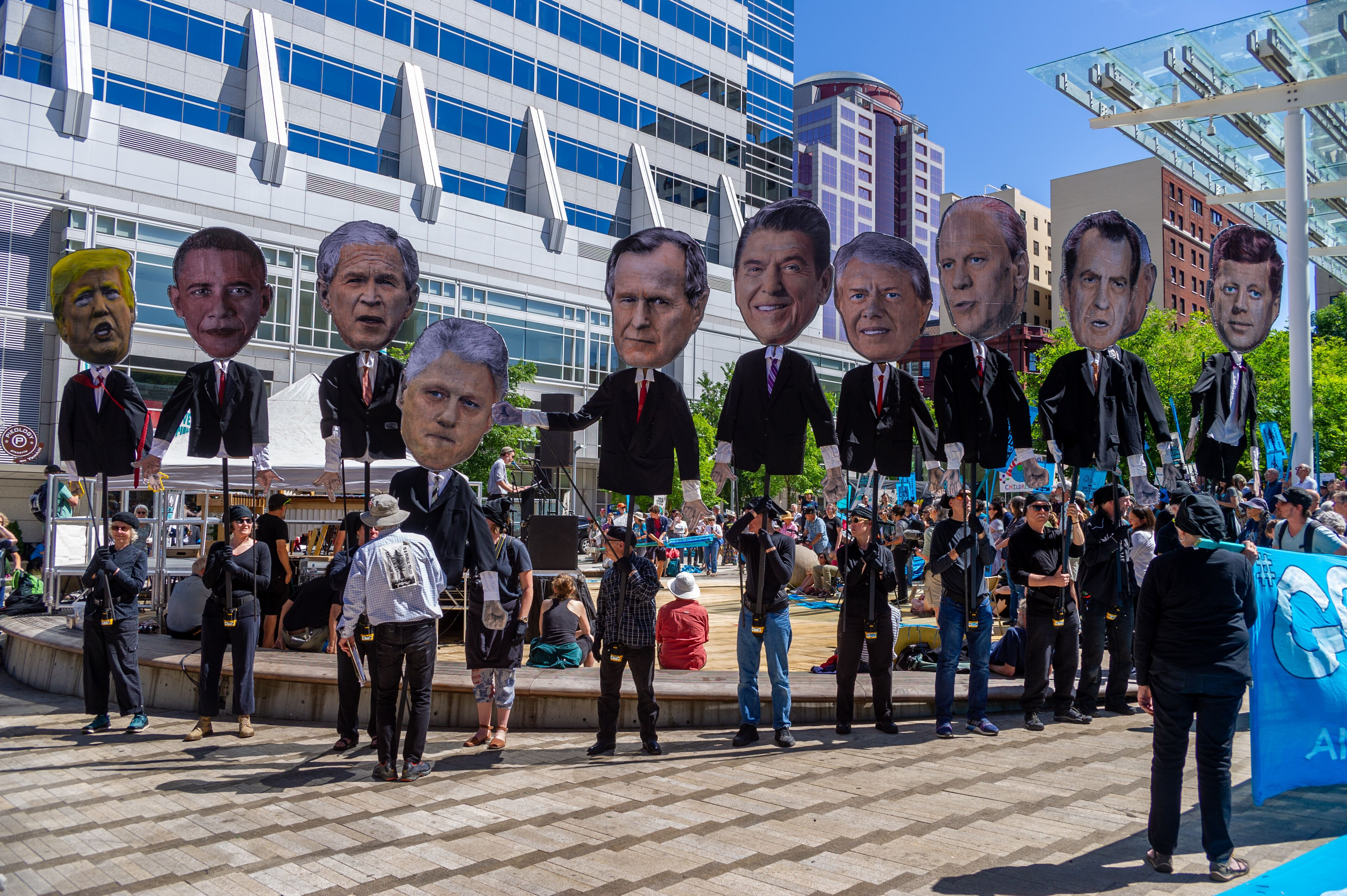 Past U.S. presidents are held up at a rally in Portland in support of a Supreme Court case in which young people are suing th