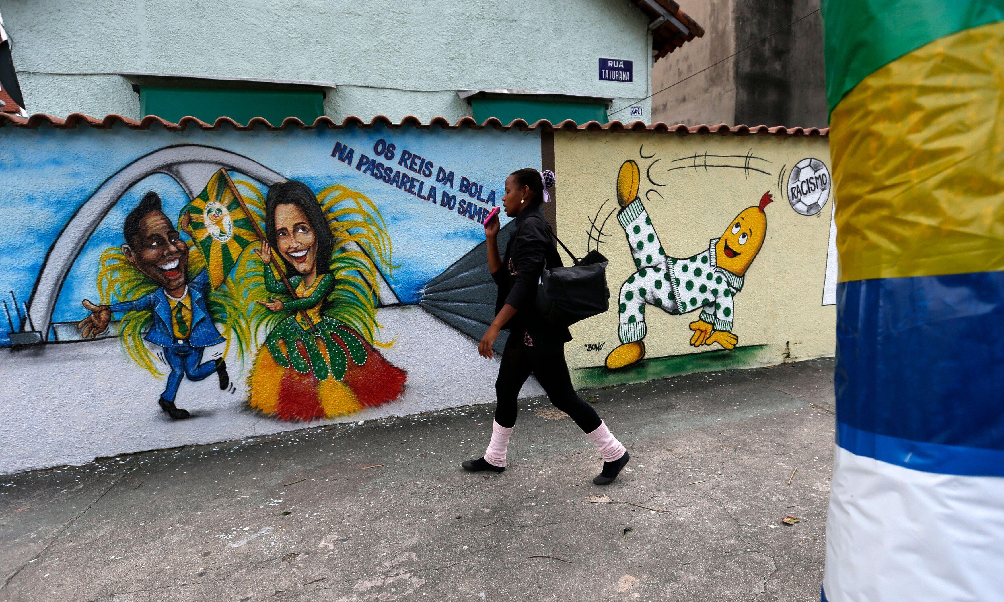 A woman walks past graffiti depicting Brazilian soccer superstars Pelé, left, and Marta, right, ahead of the 2014 Worl