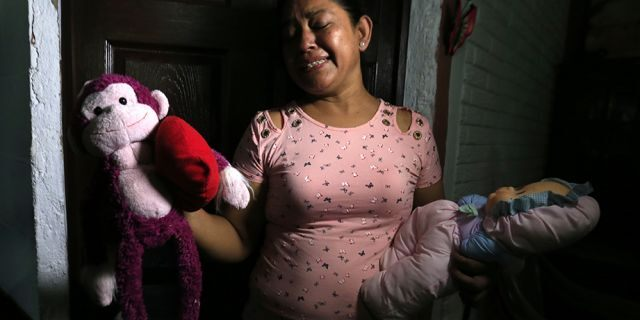 Rosa Ramirez sobs as she shows journalists toys that belonged to her nearly 2-year-old granddaughter Valeria in her home in San Martin, El Salvador, on Tuesday. (AP)