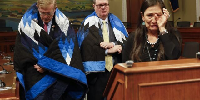 Rep. Deb Haaland, D-N.M., cries while speaking as Rep. Denny Heck, D-Wash., and Rep. Paul Cook, R-Calif., listen during a news conference Tuesday, June 25, 2019, on Capitol Hill in Washington. Advocates for Native Americans called for Congress to revoke the Medals of Honor given to the U.S. soldiers who participated in the Wounded Knee massacre. (AP Photo/Kali Robinson)