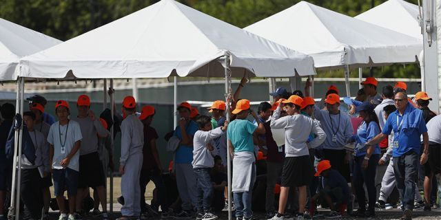 Migrant children stand outside the Homestead Temporary Shelter for Unaccompanied Children in Homestead, Fla, in May.