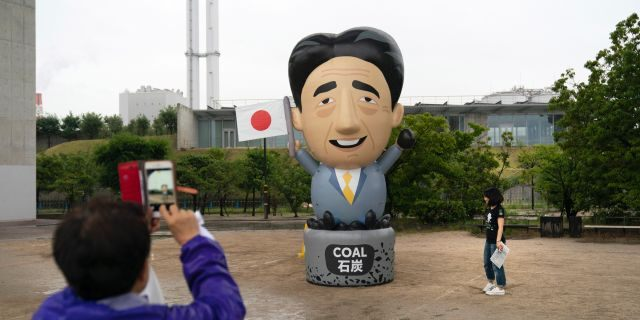 A large inflatable depicting Japanese Prime Minister Shinzo Abe stands in front of a coal-fired power plant during a priests held to demand an to coal funding ahead of the G20 Summit Thursday, June 27, 2019, in Kobe, Japan. (AP Photo/Jae C. Hong)