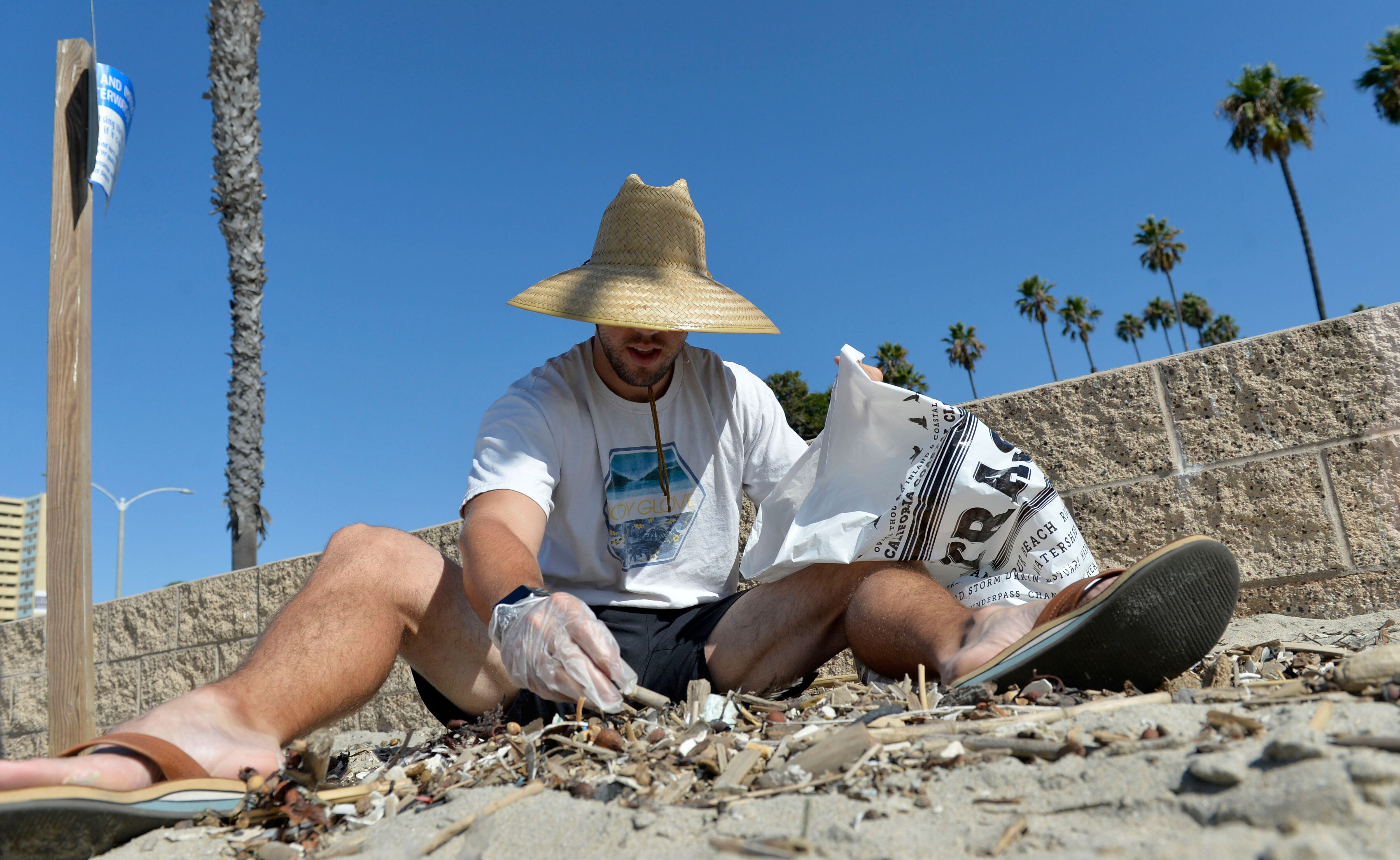 A volunteer sifts through debris, picking out cigarette butts on Coastal Cleanup Day on September 15th, 2018 in Long Beach, C
