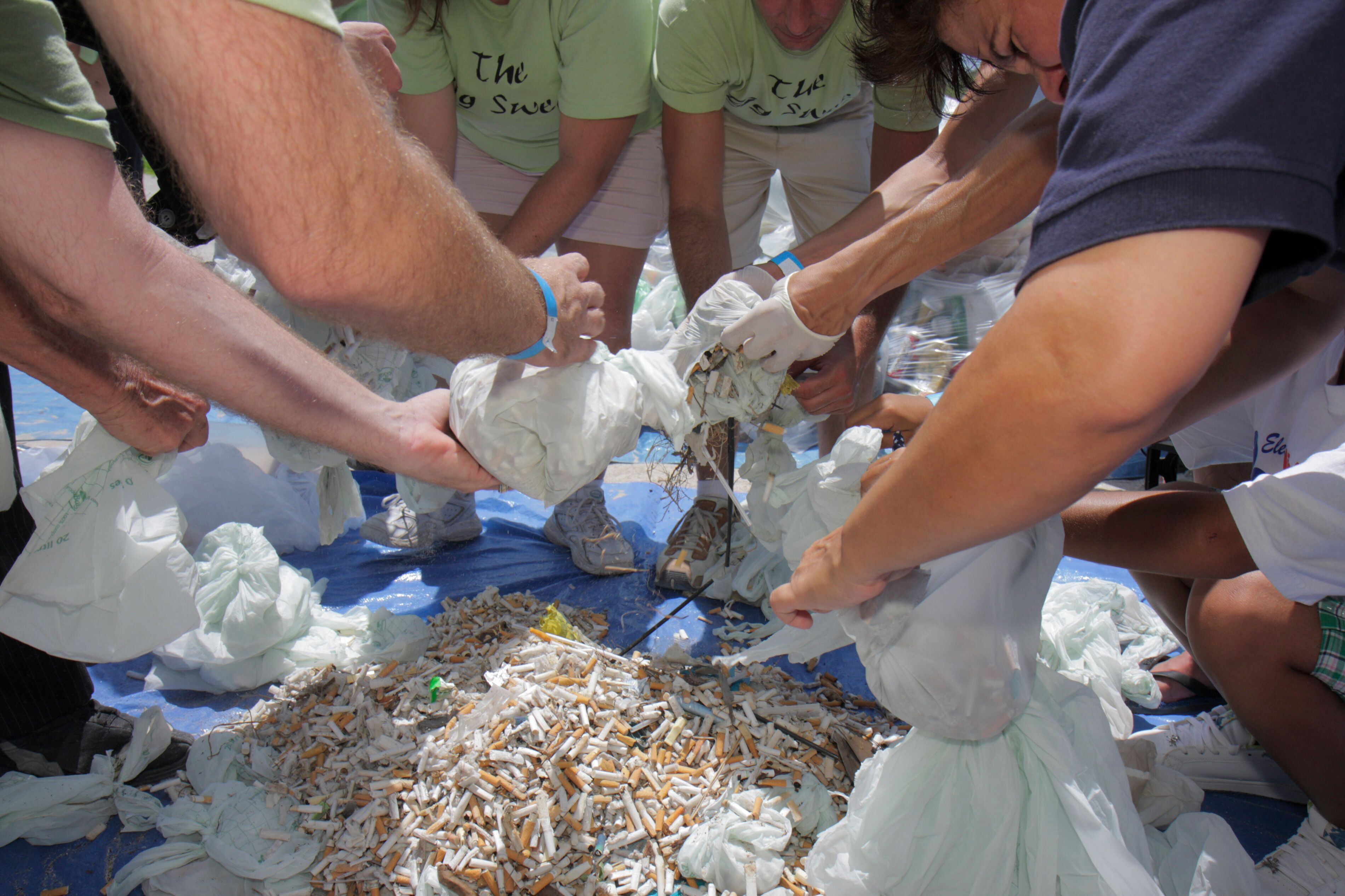 Volunteers fill bags with cigarette butts found on Miami Beach at the ECOMB Big Sweep Plastic a decade ago.