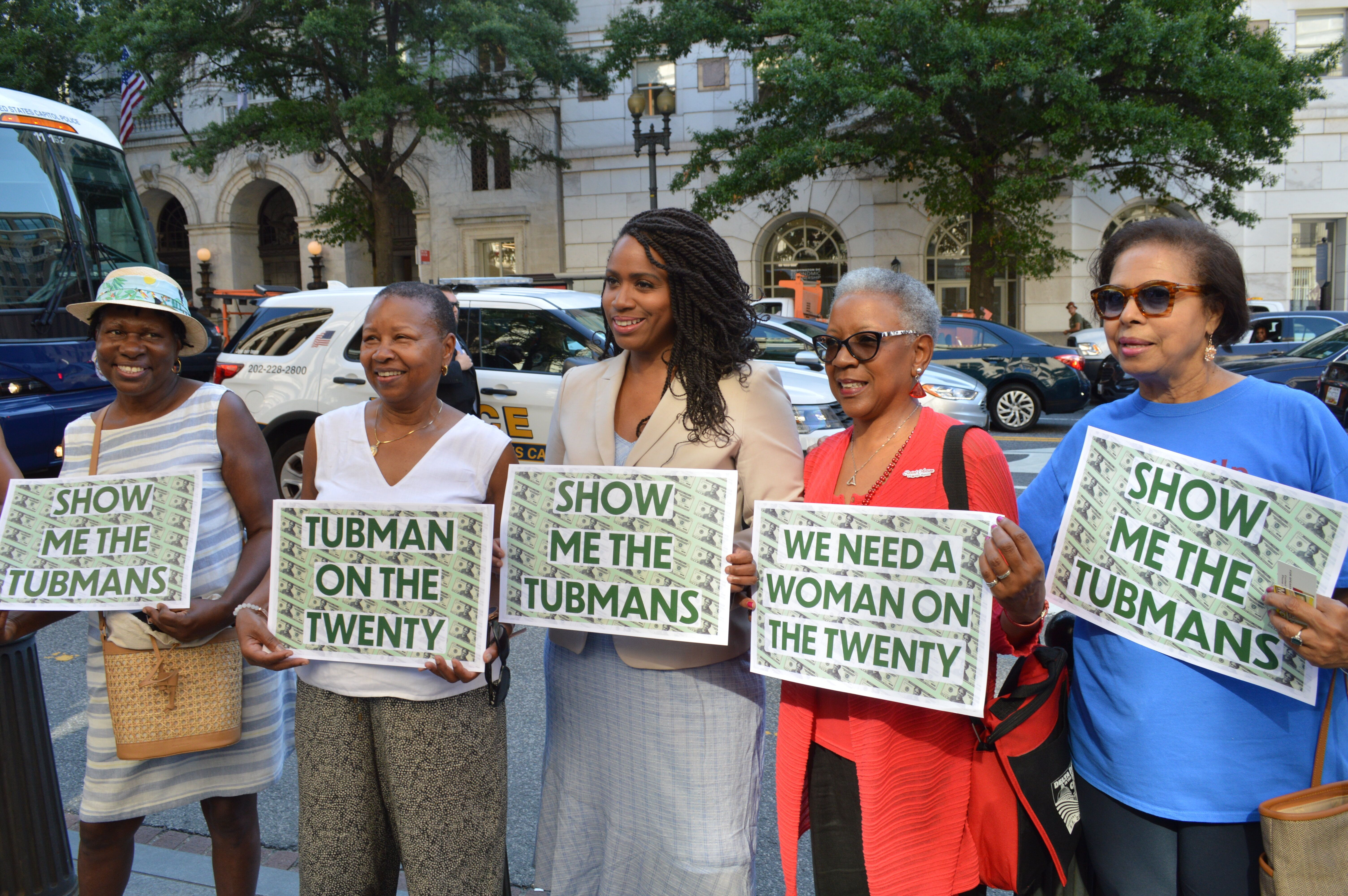 Rep. Ayanna Pressley (D-Mass.), center, holds up signs with supporters that call for Harriet Tubman to be put on the $20 bill