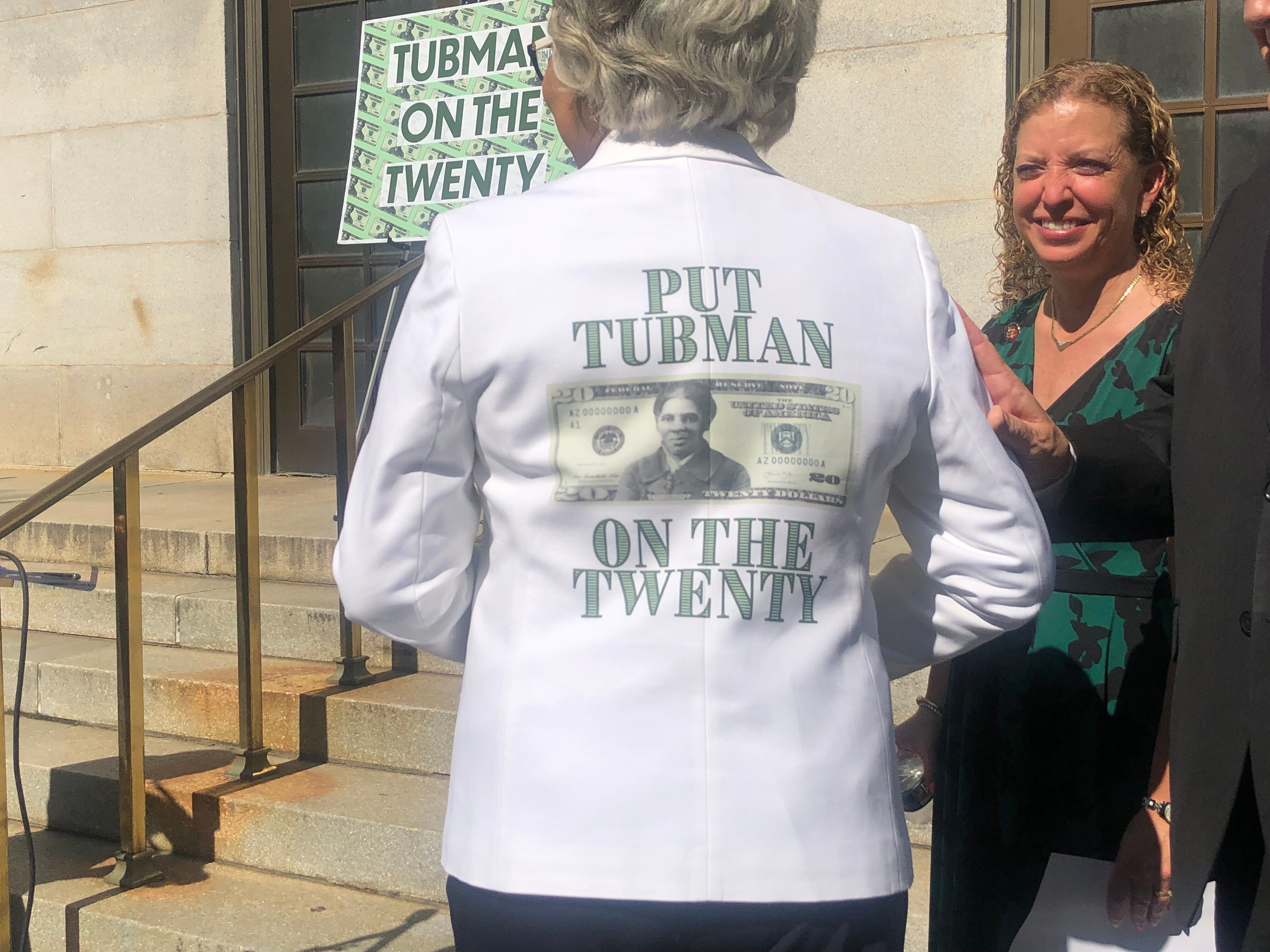 """Rep. Joyce Beatty (D-Ohio) turns around to display the back of her suit jacket that says: """"Put Tubman On The Twenty"""" with a m"""