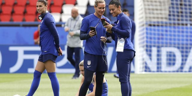 United States' Alex Morgan, left, walks past, her teammates Ashlyn Harris, center, and Ali Krieger during a visit at the Parc des Princes stadium a day before the Group F soccer match between United States and Chile. (AP Photo/Alessandra Tarantino)