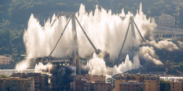 A cloud of dust rises as the remaining spans of the Morandi bridge are demolished in a planned explosion, in Genoa, Italy, Friday, June 28, 2019. (AP Photo/Antonio Calanni)