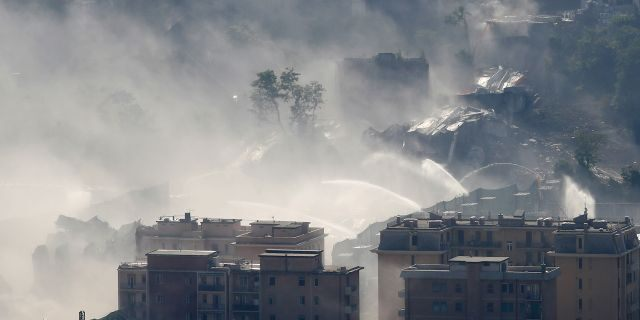 Fire hoses spray water to reduce dust triggered by the planned blast which demolished the remaining spans of the Morandi bridge, in Genoa, Italy, Friday, June 28, 2019. (AP Photo/Antonio Calanni)