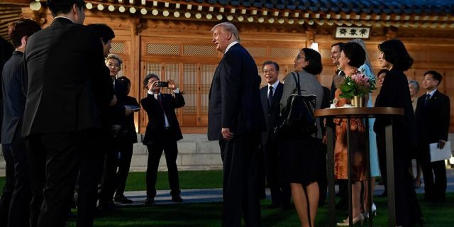 President Donald Trump, center, talks with guests including members of the band Exo during a visit with South Korean President Moon Jae-in at the tea house on the grounds of the Blue House in Seoul, South Korea, Saturday, June 29, 2019. Trump is making a quick trip to Seoul after attending the G-20 summit in Osaka, Japan.