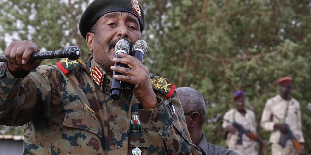 """FILE - In this June 29, 2019, file photo, Sudanese Gen. Abdel-Fattah Burhan, head of the military council, speaks during a military-backed rally, in Omdurman district, west of Khartoum, Sudan. An African Union envoy says Sudan's ruling military council and the country's pro-democracy movement have reached a power-sharing agreement, including a timetable for a transition to civilian rule. Mohammed el-Hassan Labat said early Friday, July 5, that both sides agreed to form a joint sovereign council that will rule the country for """"three years or a little more."""" The sides agreed to five seats for the military and five for civilians with an additional seat going to a civilian with military background.(AP Photo/Hussein Malla, File)"""