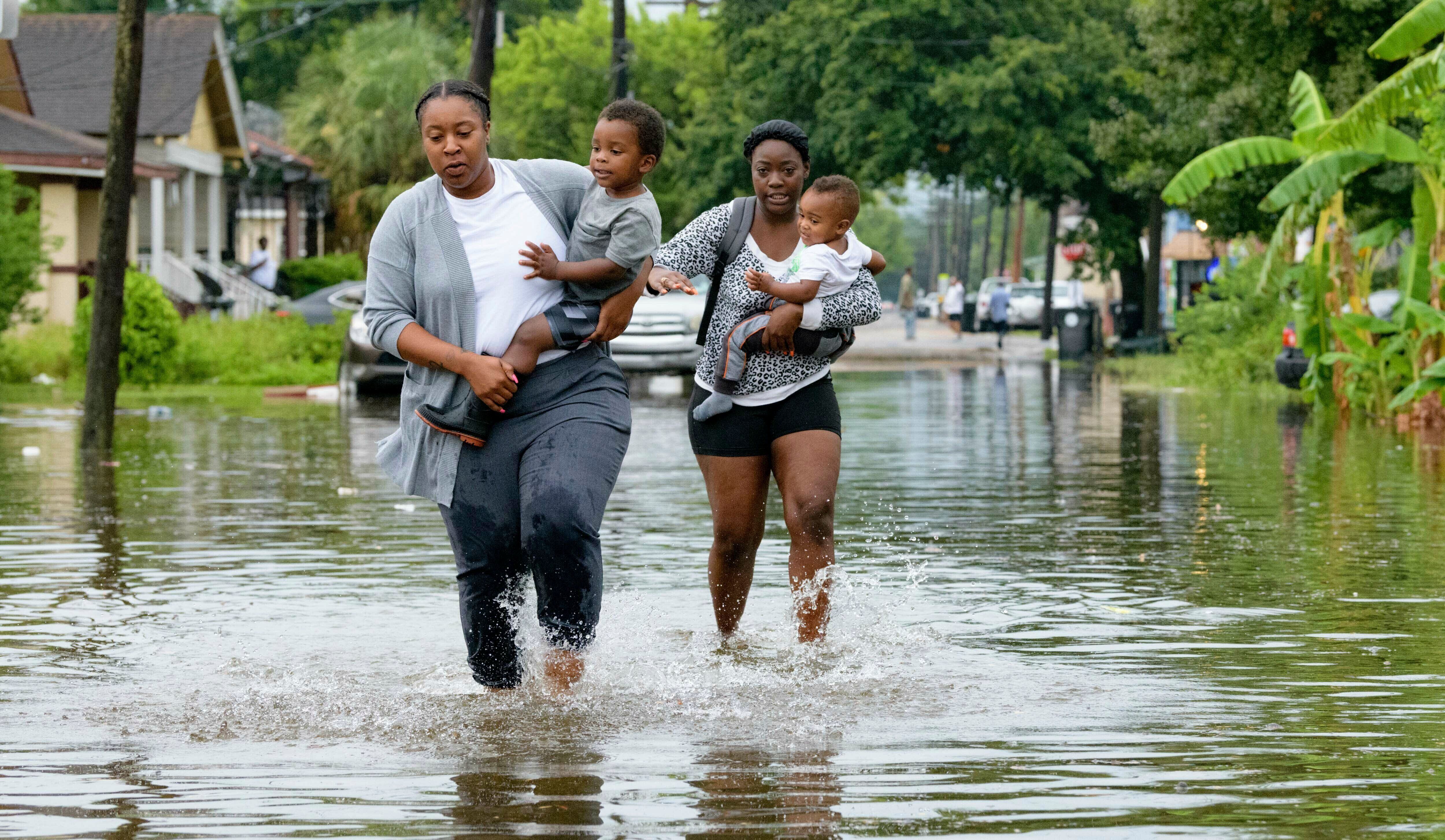Jalana Furlough carries her son Drew Furlough as Terrian Jones carries Chance Furlough in New Orleans after flooding Wednesda