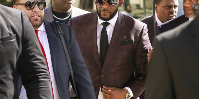 R&B singer R. Kelly, center, arrives at the Leighton Criminal Court building for an arraignment on sex-related felonies in Chicago.