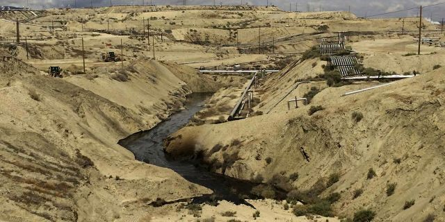 In this May 10, 2019 photo provided by the California Department of Fish and Wildlife's Office of Spill Prevention and Response, oil flows at a Chevron oil field in Kern County, Calif. Nearly 800,000 gallons of oil and water has seeped from the ground since May. (California Department of Fish and Wildlife's Office of Spill Prevention and Response via AP)