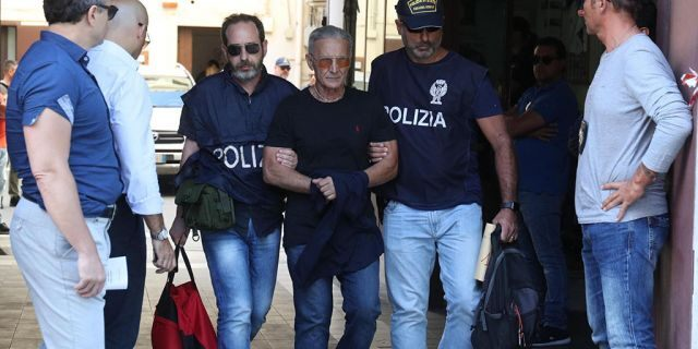 Suspect Rosario Gambino, center, is taken into custody during an anti-mafia operation lead by the Italian Police and the FBI in Palermo, Southern Italy, Wednesday, July 17, 2019. Italian police and the FBI arrested 19 suspected Mafiosi in a joint operation Wednesday following an investigation which revealed alleged ties between Sicily's Cosa Nostra Mafia and New York's Gambino crime family.