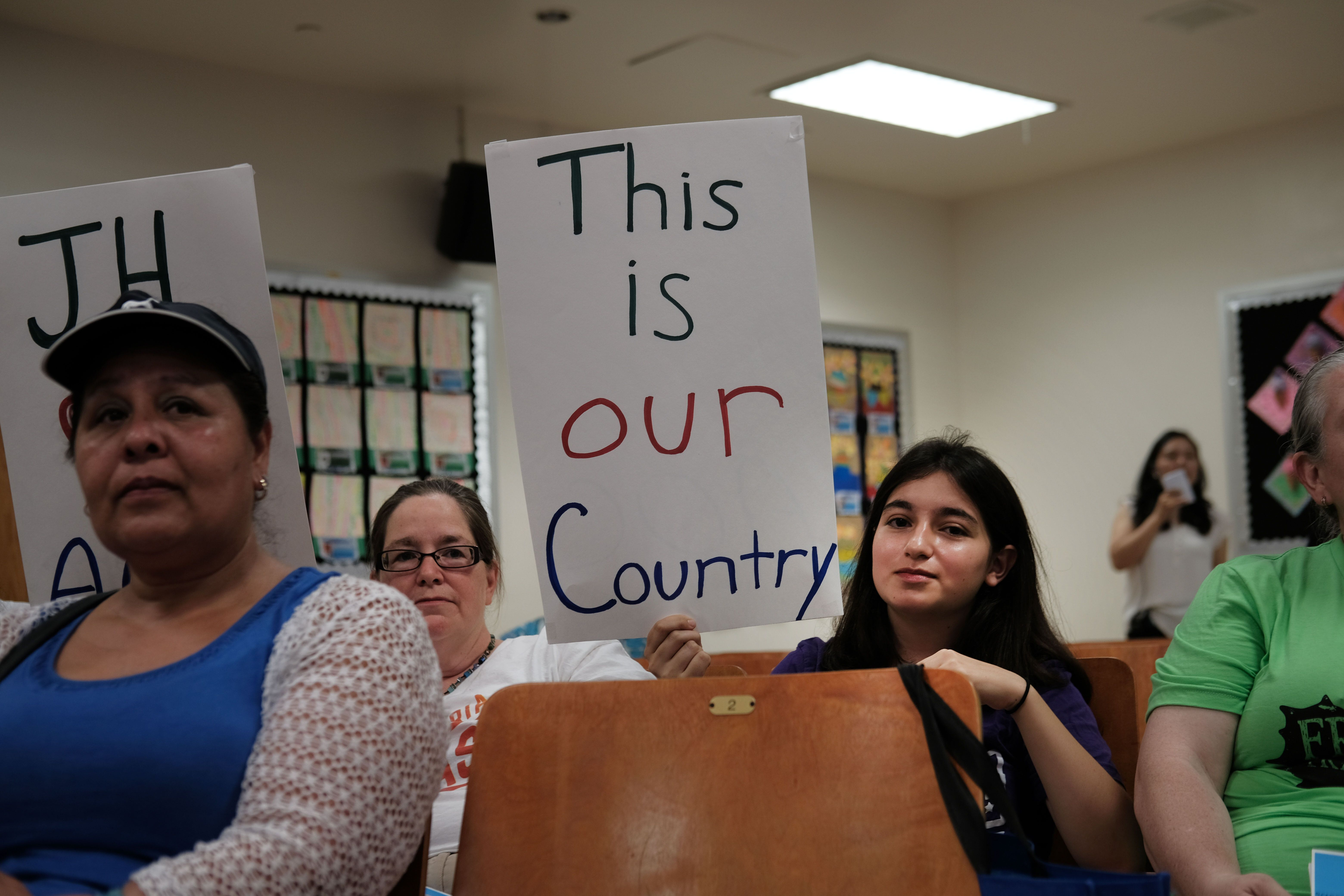 Some of Ocasio-Cortez's diverse constituents brought home-made signs to an immigration town hall on Saturday.