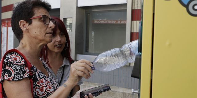 Tourist information hostess Elisa Bulzomi, right, explains to a passenger how to insert a plastic bottle into an automatic recycling bin outside a subway station in Rome, Wednesday, July 24, 2019.