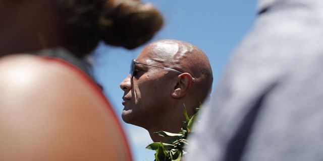 """Actor Dwayne """"The Rock"""" Johnson stands during a prayer during a visit to the protests against the TMT telescope, Wednesday, July 24, 2019, at the base of Mauna Kea on Hawaii Island. (Jamm Aquino/Honolulu Star-Advertiser via AP)"""