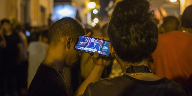 Locals listen on a smartphone to the pre-recorded message by Puerto Rico Gov. Ricardo Rossello announcing that he is resigning Aug. 2 after weeks of protests over leaked obscene, misogynistic online chats, in San Juan, Puerto Rico, Wednesday, July 24, 2019. (Associated Press)