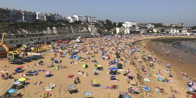 People flock to Broadstairs beach in Kent, England, Thursday July 25, 2019.