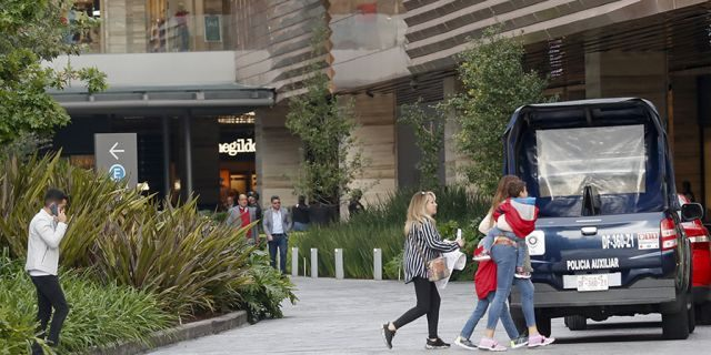 "People leave an upscale shopping mall in the south of Mexico City, Wednesday, July 24, 2019, where a woman wearing a blond wig disguise killed two Israeli men. Authorities said the woman and another man sat down at a table near the victims before she rose and shot the two Israelis at close range. According to Mexico City police chief Jesus Orta the woman said, ""she had a sentimental relationship with one of the victims, who she met on social media, and that the attack was due to infidelity."" (AP Photo)"