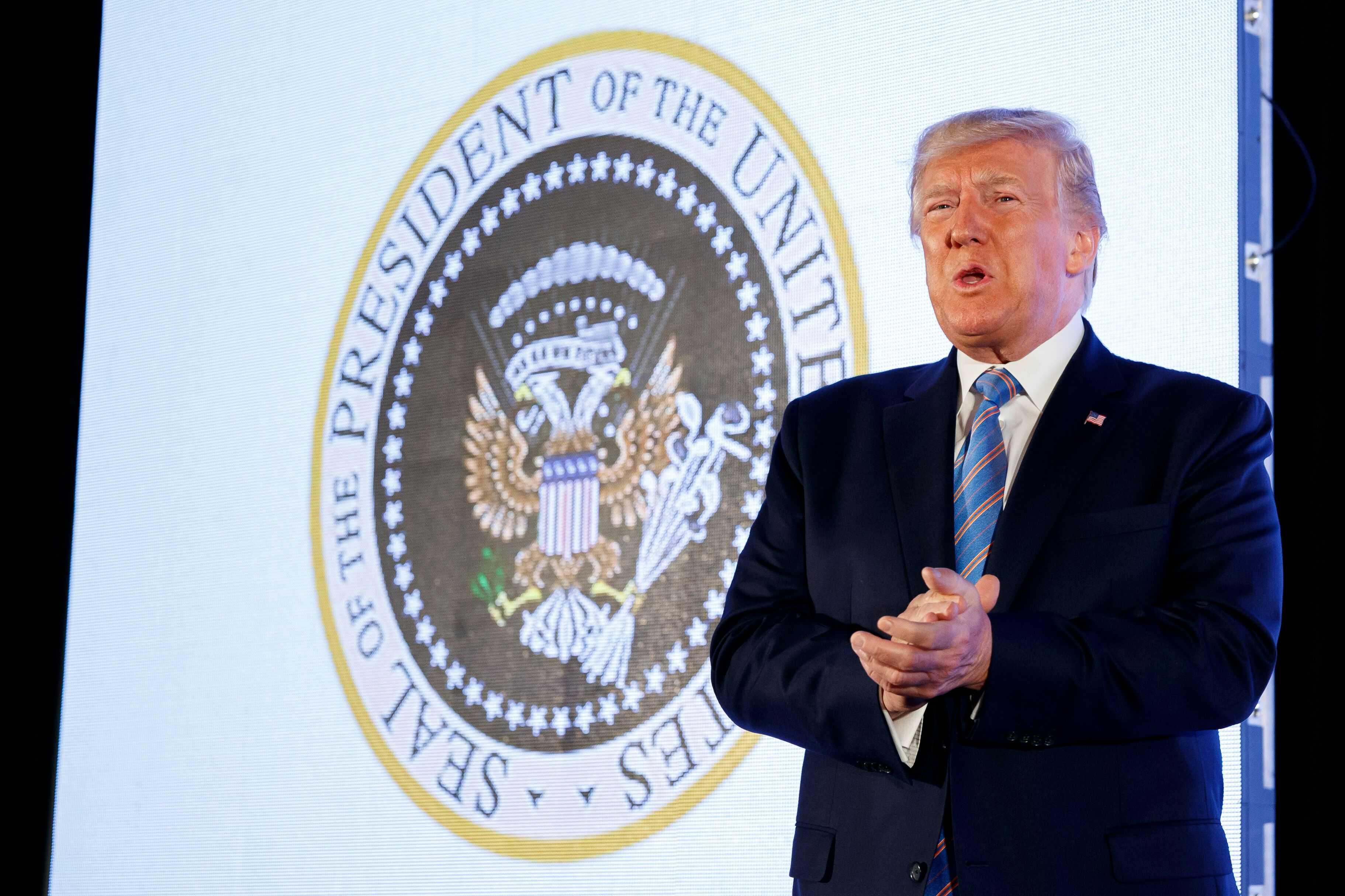 President Donald Trump speaks to a college Republican group as the doctored presidential seal showing Russian symbols and gol