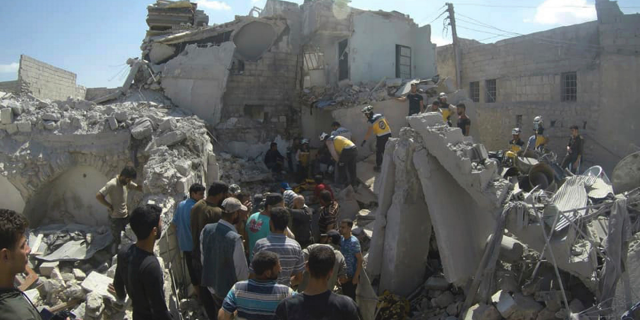 This photo provided by the Syrian Civil Defense White Helmets, which has been authenticated based on its contents and other AP reporting, shows Syrian White Helmet civil defense workers searchING for victims from under the rubble of a destroyed building that hit by a Syrian government airstrike, in the northern town of Ariha, in Idlib Province, Syria, earlier this month. (Syrian Civil Defense White Helmets via AP)