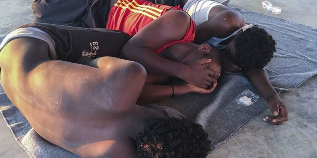 Rescued migrants rest on a coast some 100 kilometers (60 miles) east of Tripoli, Libya, Thursday, July 25, 2019. The U.N. refugee agency and the International Rescue Committee say up to 150 may have perished at sea off the coast of Libya. The country's coast guard says the Europe-bound migrants are missing and feared drowned after the boats they were traveling on capsized in the Mediterranean Sea. A spokesman says they rescued around 137 migrants on Thursday. (AP Photo/Hazem Ahmed)