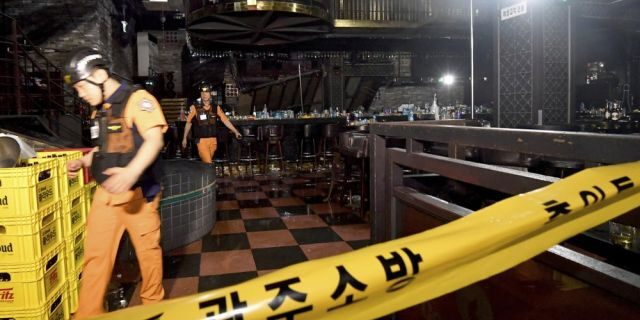 Rescue workers walk to inspect a collapsed internal balcony at a nightclub in Gwangju, South Korea, Saturday, July 27, 2019. Members of the U.S. national water polo team were in a South Korean nightclub on Saturday when an internal balcony collapsed, killing at least one person. (Associated Press)