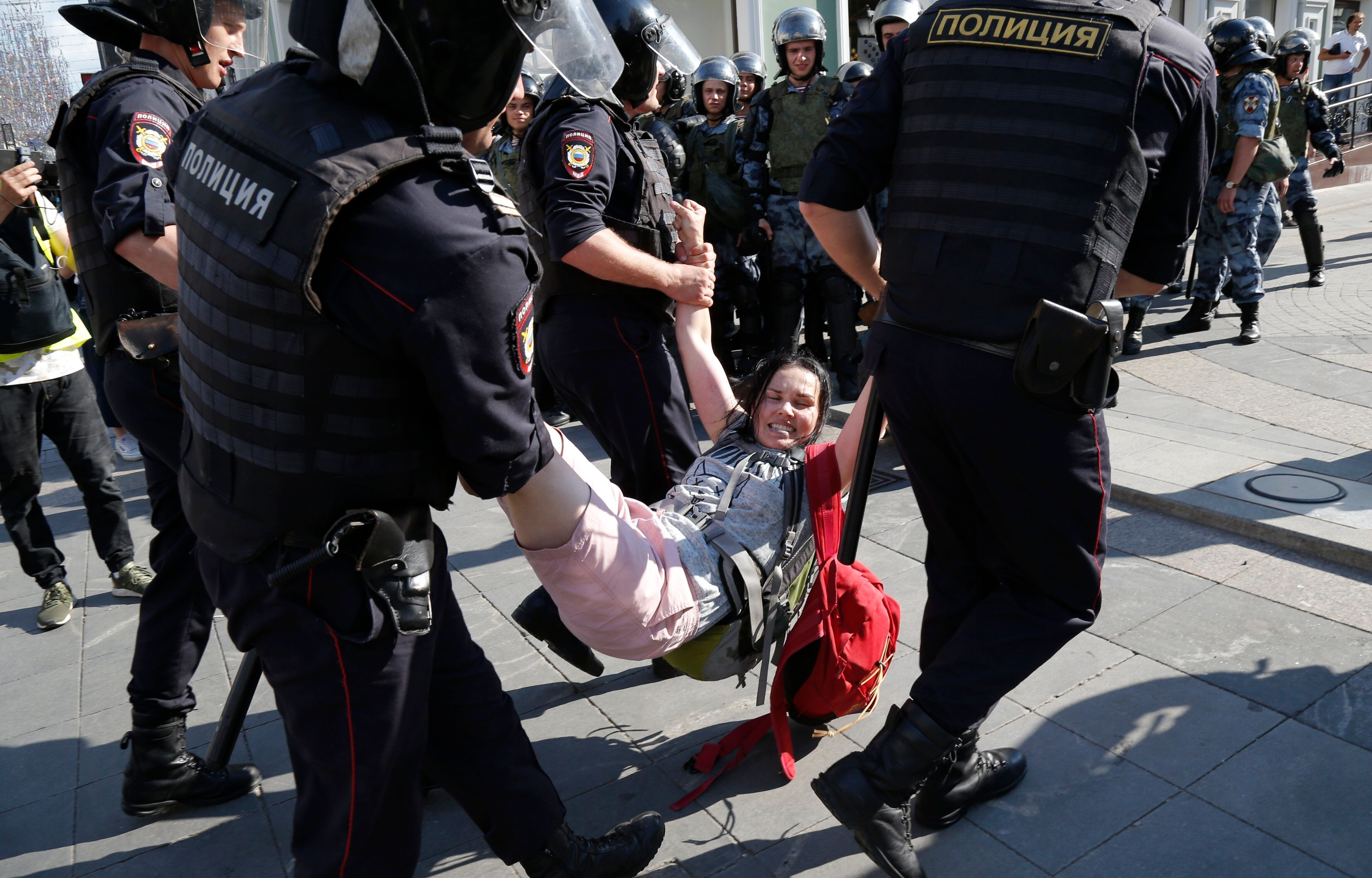 Police officers detain a woman during an unsanctioned rally in the center of Moscow, Russia, Saturday, July 27, 2019. Russian