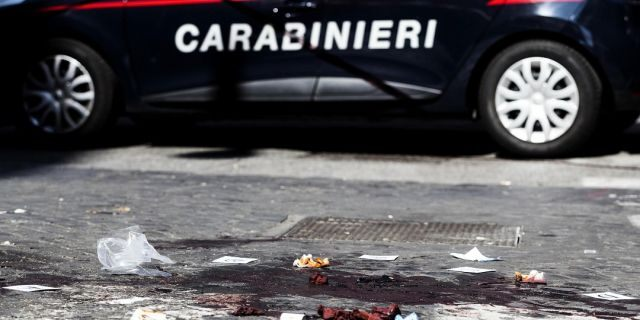 A car of the Italian Carabinieri, paramilitary police, is parked near a blood stain, the site where Carabiniere Vice Brigadier Mario Cerciello Rega was stabbed to death by a thief in Rome on Friday. (Angelo Carconi/ANSA Via AP)