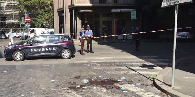 Two Italian Carabinieri, paramilitary police officers, stand near a blood stain, the site where their colleague, Carabiniere Vice Brigadier Mario Cerciello Rega, was stabbed to death by a thief in Rome. (Associated Press)