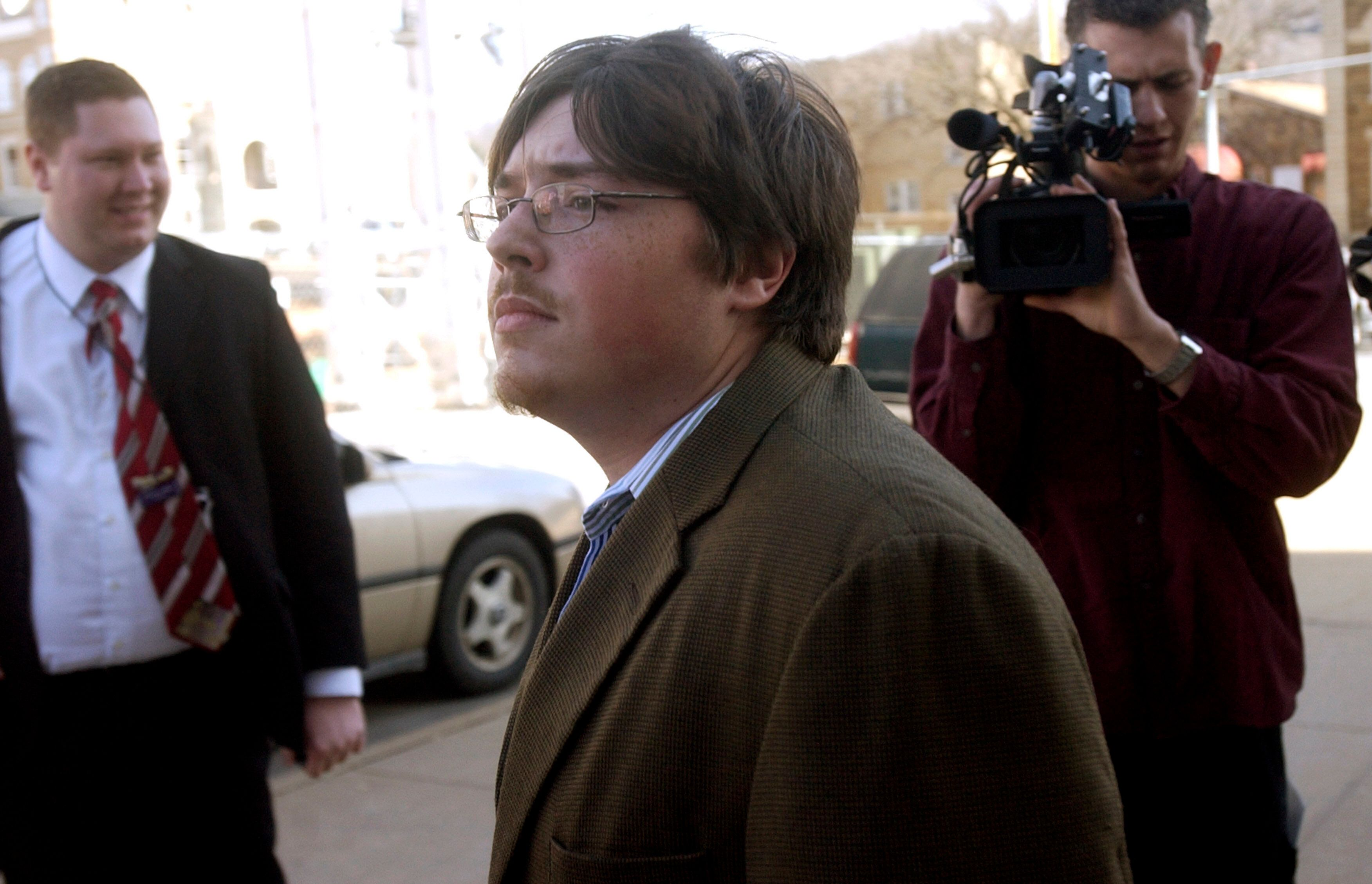 Johnson (center) walks past members of the media during his 2008 trial in Fayetteville, Arkansas, forpossession of a fi