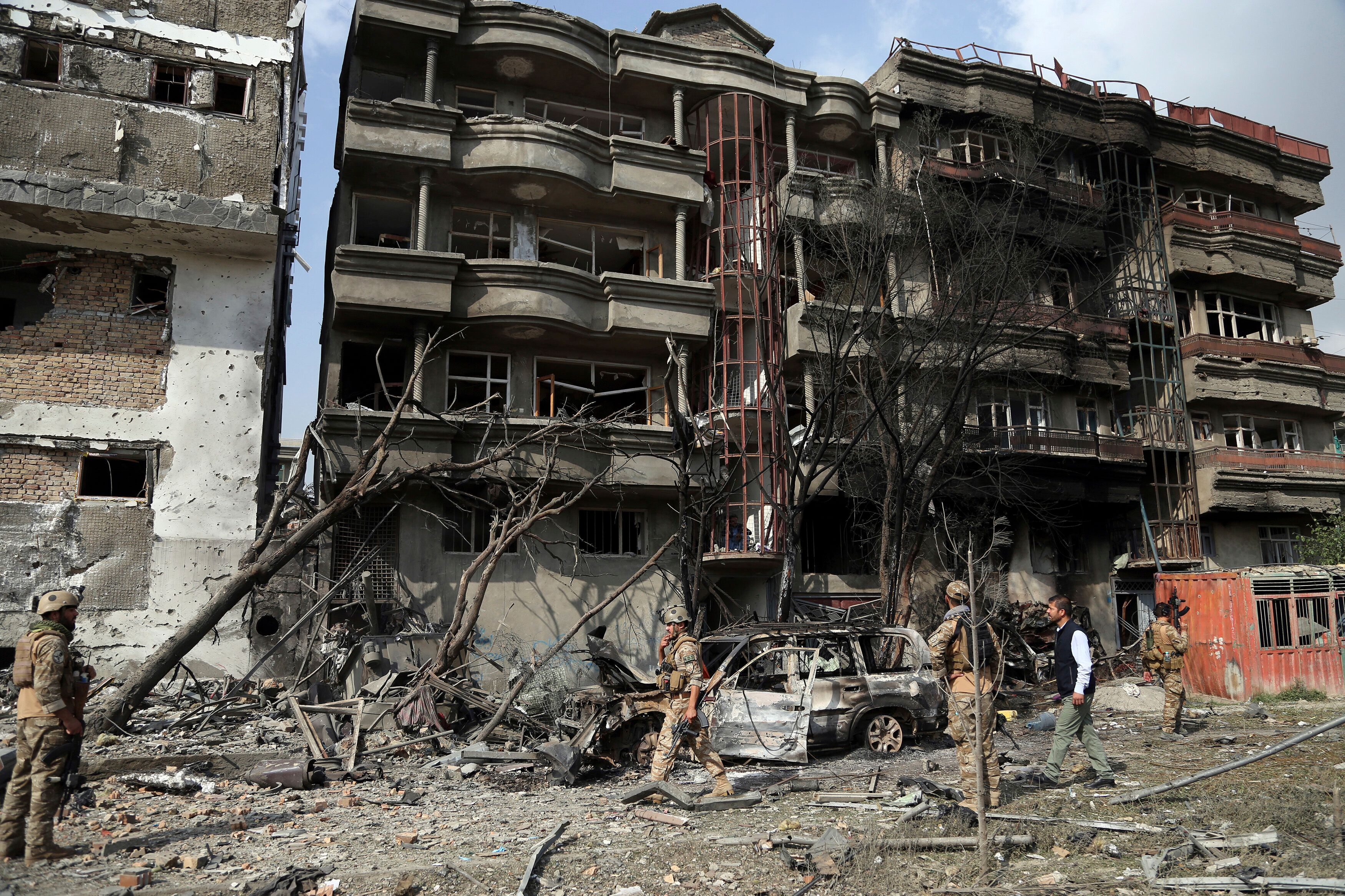 Afghan security forces inspect the aftermath of Sunday's attack against the office of the president's running mate in Kabul.